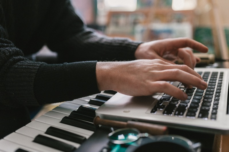 young man editing music with his laptop set ontop of a keyboard piano